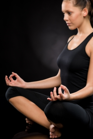 Side view of relaxed young woman exercising in lotus position Stock Photo - 17160298