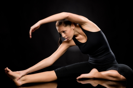 yoga pants: Brunette young woman exercising yoga in separate leg stretching pose Stock Photo