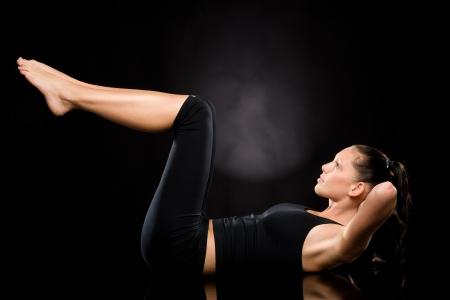 haciendo ejercicio: Mujer haciendo ejercicio de estiramiento con las piernas elevadas sobre el suelo Foto de archivo