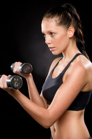 half  length: Half length of a young woman lifting dumbbells in sportswear Stock Photo