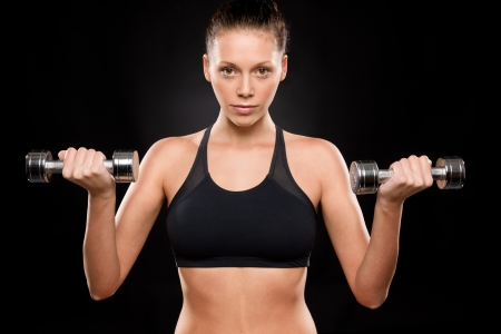 Portrait of a sporty woman lifting weights with both hands Stock Photo - 17160274