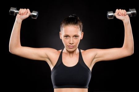 Attractive young brunette woman lifting dumbbells over her head pose Stock Photo - 17160294