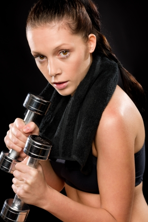 Sporty young woman exercising lifting weights with towel behind neck Stock Photo - 17160257