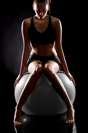 Young Caucasian woman exercising on fitness ball wearing gym wear Stock Photo - 17160259