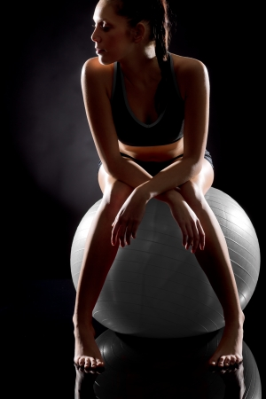 Young sporty woman relaxing on fitness ball on black background Stock Photo - 17160262