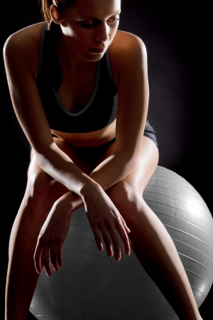 Thoughtful young woman relaxing on fitness ball on black background Stock Photo - 17160243