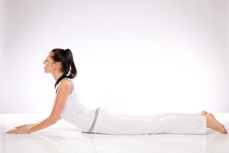 Young Caucasian woman lying in yoga position on white background photo
