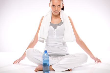 Young woman sitting cross legged after exercises with a bottle Stock Photo - 17160295