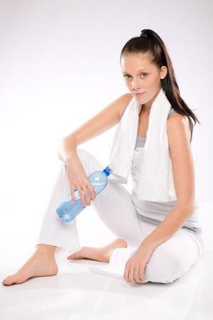 Thirsty pretty slim woman relaxing after exercises on white background Stock Photo - 17160286