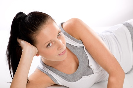 Young Caucasian tired woman lying in sportswear on white background Stock Photo - 17160269