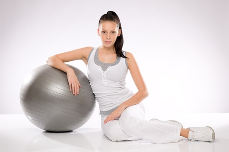 Young Caucasian woman leaning on fitness ball on white background Stock Photo - 17160291