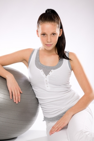 large ball: Woman relaxing after exercises with fitness ball on white background