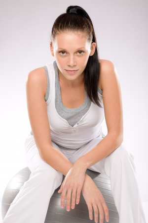 Sporty brunette young woman sitting on fitness ball after exercises Stock Photo - 17160264