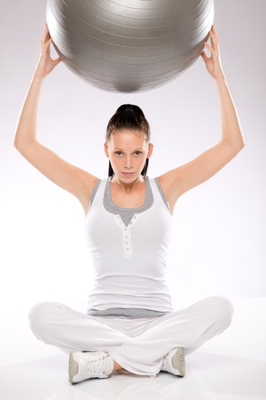 Young woman sitting and holding fitness ball above her head Stock Photo - 17160266
