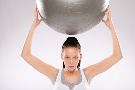 Portrait of young woman exercising with fitness ball held above Stock Photo - 17160275