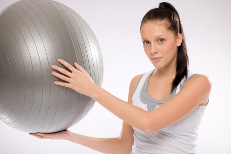 fit ball: Young Caucasian brunette woman holding fitness ball on white background Stock Photo
