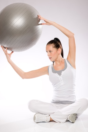 Slim young woman exercising with fitness ball from sitting position photo