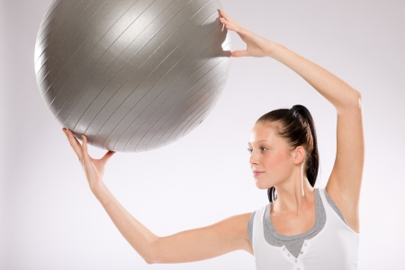 Young woman doing exercises with fitness ball on white background Stock Photo - 17160245