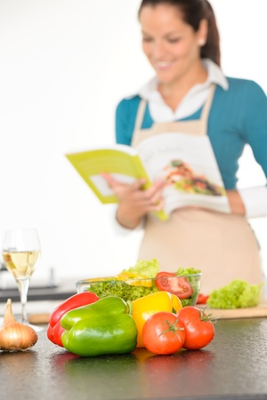 Happy woman preparing recipe vegetables wine kitchen cooking book Stock Photo - 17388959