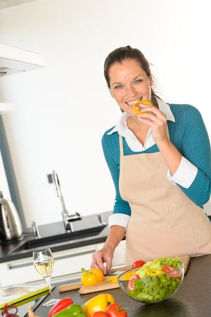 Young woman tasting preparing vegetables food dinner kitchen happy salad Stock Photo - 17388940