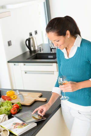 Woman using tablet recipe book searching kitchen wine vegetables photo