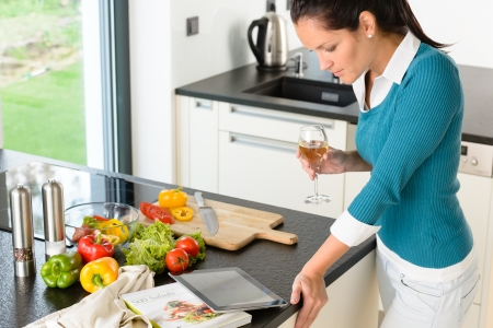 Young woman reading tablet recipe kitchen preparing food looking wine Stock Photo - 17388883