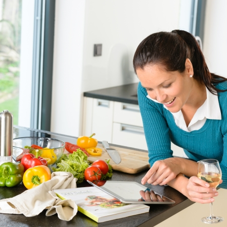 Smiling woman searching recipe tablet kitchen cooking food vegetables photo