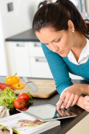 Young woman looking tablet recipe kitchen vegetables preparing food photo