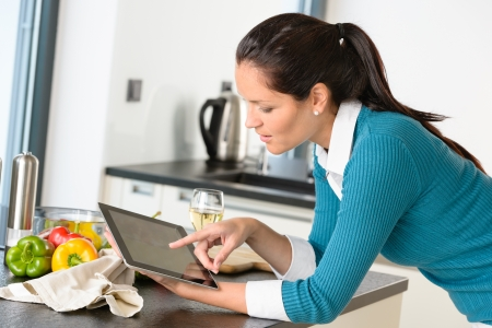 Young woman reading recipe tablet searching kitchen preparing vegetables Stock Photo - 17388889