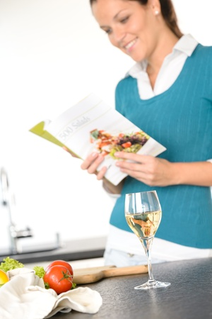 Young woman reading recipe cooking book preparing salad wine kitchen