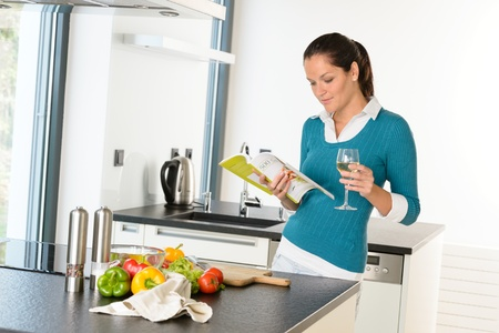Woman housewife reading cooking book recipe kitchen wine vegetables