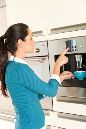 with coffee maker: Young woman setting coffee maker machine kitchen cup Stock Photo