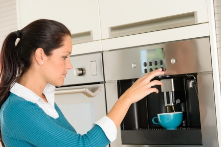 Happy young woman making coffee cup machine kitchen interior Stock Photo