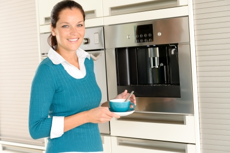 with coffee maker: Smiling woman drinking cappuccino kitchen machine cup home interior Stock Photo