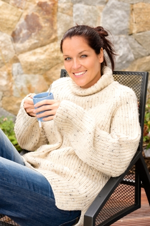 Smiling woman drinking tea relaxing patio sitting sweater Stock Photo - 17388894