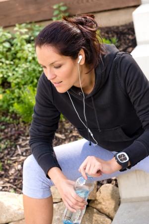 sweatsuit: Tired woman relaxing after running sport bottle headphones sweatsuit Stock Photo