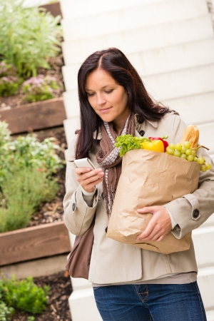 Young woman holding bag groceries vegetables shopping smart phone texting photo