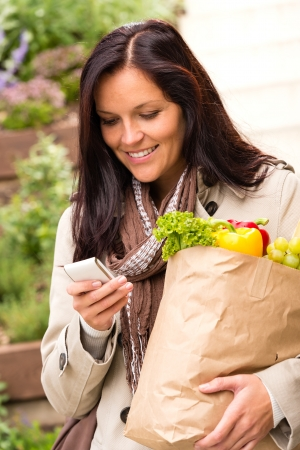 Smiling woman shopping vegetables mobile phone groceries messaging sms photo