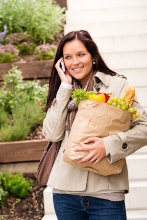 Happy woman shopping vegetables calling cell phone paper bag Stock Photo - 17388891