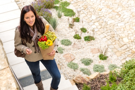 arriving: Young woman arriving home groceries shopping smiling garden standing Stock Photo