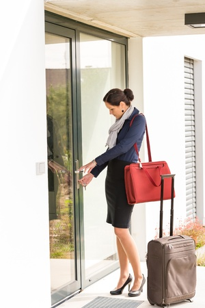 hurried: Young businesswoman locking door traveling luggage leaving home bag