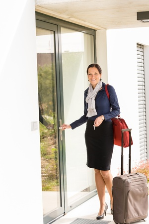 leaving: Smiling woman business flight attendant arriving home baggage door traveling