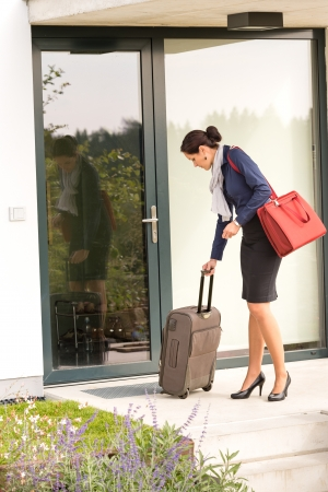hurried: Businesswoman leaving house traveling carrying baggage hurried busy rushing