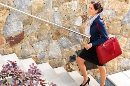 subiendo escaleras: Sonriente mujer escalada escalera llevar equipaje de viaje llegando