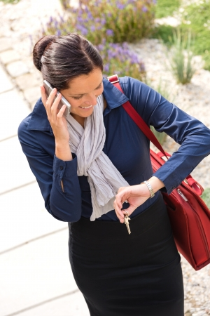 hurried: Woman calling rushing arriving home keys smart phone elegance business Stock Photo