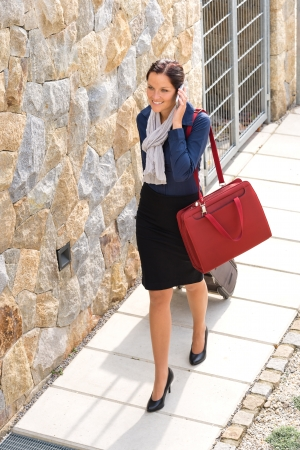 hurried: Elegance woman leaving home luggage calling phone businesswoman busy going
