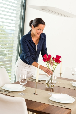 placing: Young woman placing flowers dinner table romantic Stock Photo