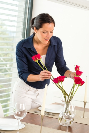 placing: Young woman arranging flowers dinner table preparation Stock Photo