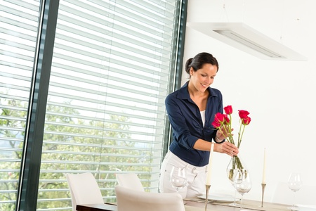 a blind: Smiling woman putting red roses dinner room