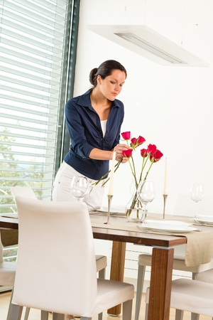 Woman decorating red roses dining room wife romantic Stock Photo